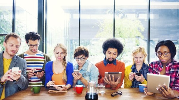 A group of Millennials sitting around a table looking at their phones