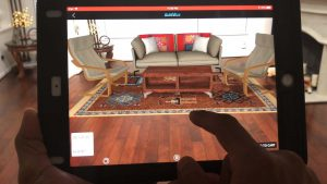A person using a tablet to place virtual furniture into a real room