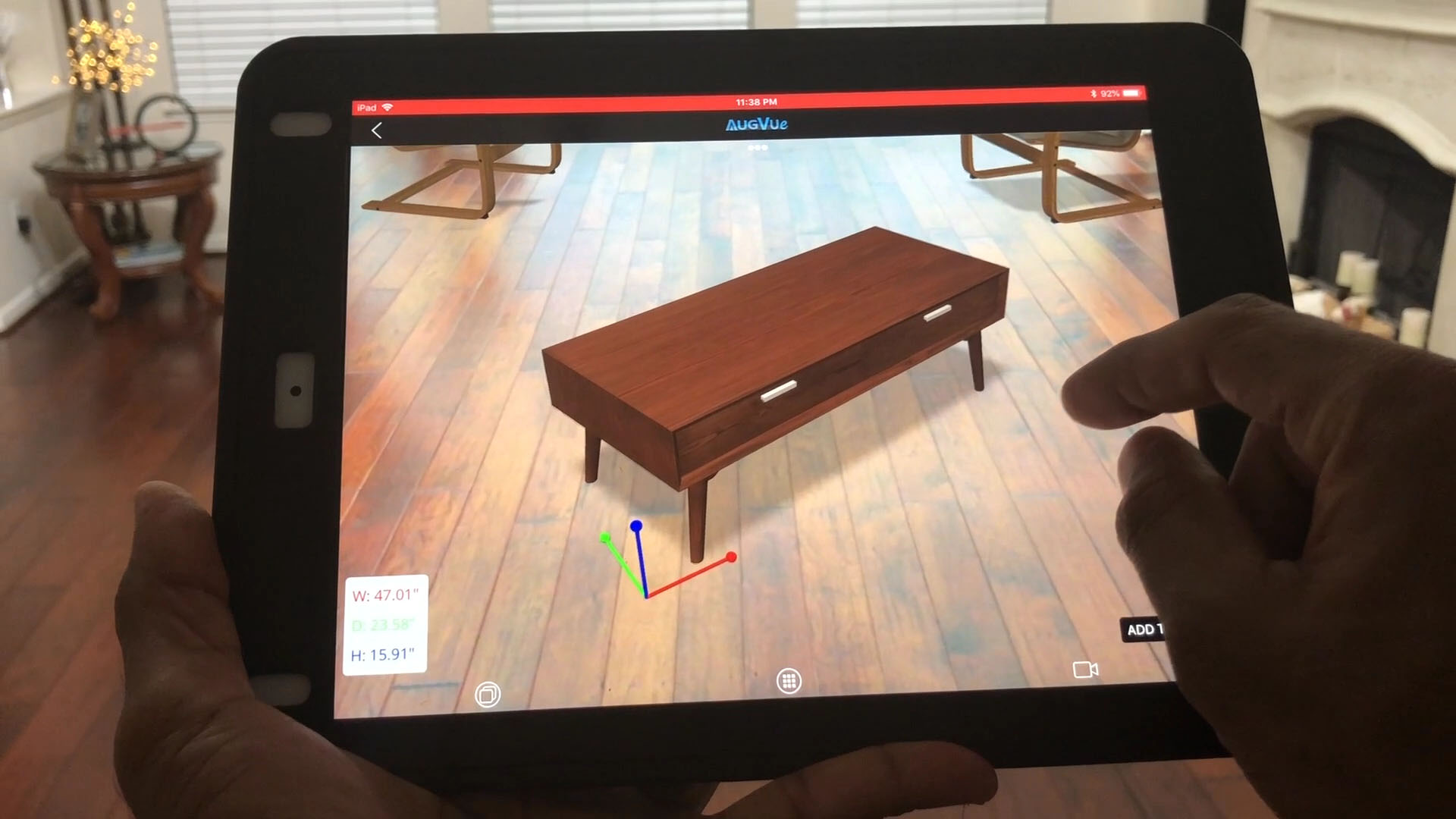 A tablet being held by a person with a virtual coffee table displaying in the person's room