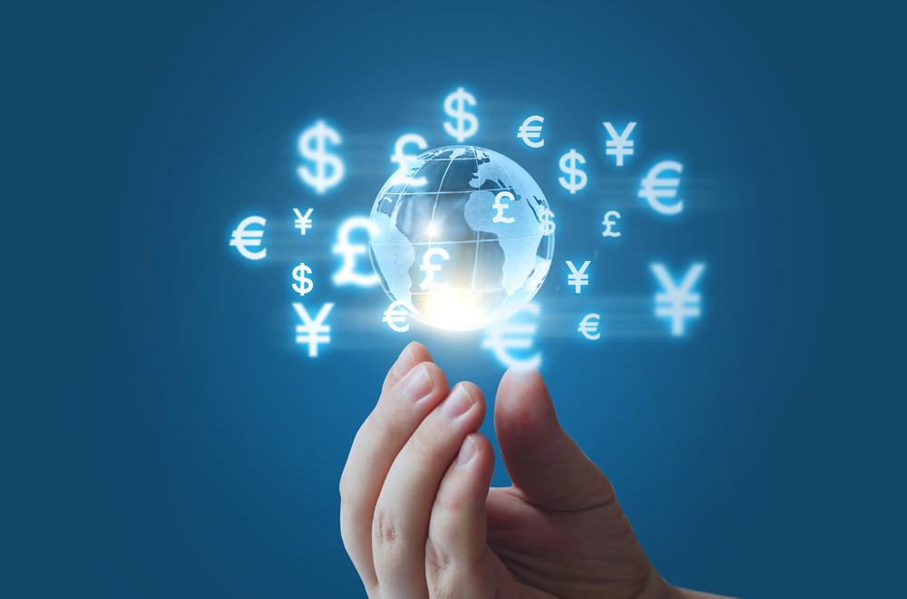 A hand holding a hologram representing the globe and different currencies