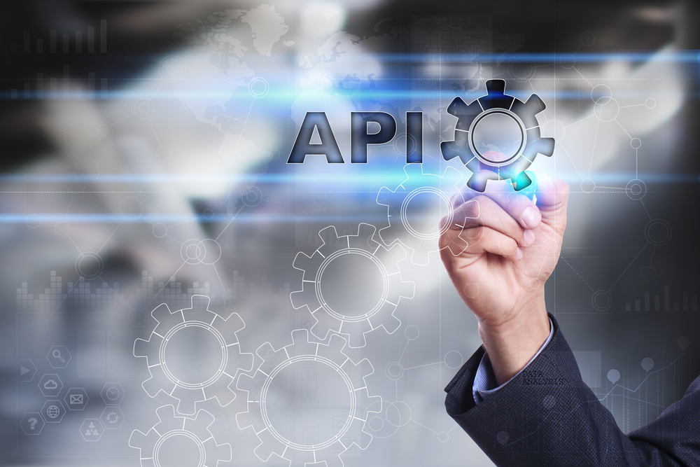 Several gears connecting together and a man's had spelling out API